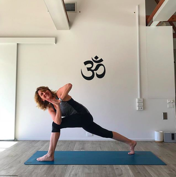 TriBalance female yoga student Ros Quivooy in revolved lunge pose on blue yoga mat