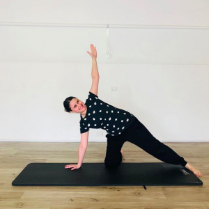 TriBalance Physiolates student Melinda Gagen in side plank on black Pilates mat