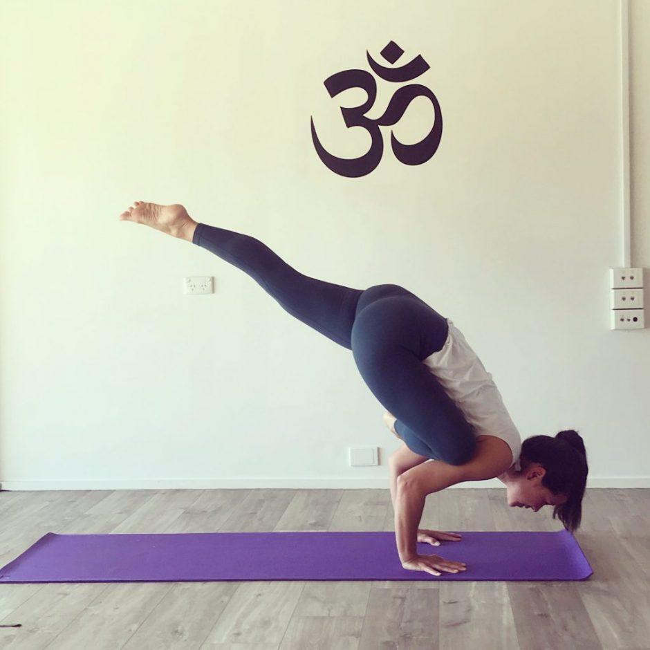 TriBalance yoga student Eleanor Blaney in flying pigeon pose on purple yoga mat