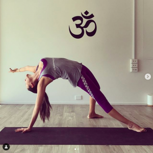 TriBalance yoga teacher Lina Saenz in wild thing on black yoga mat