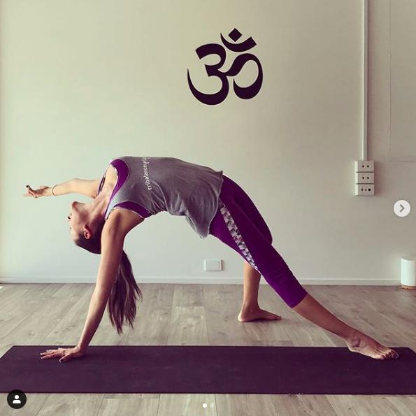 TriBalance yoga teacher Lina Saenz in wild thing on black yoga mat
