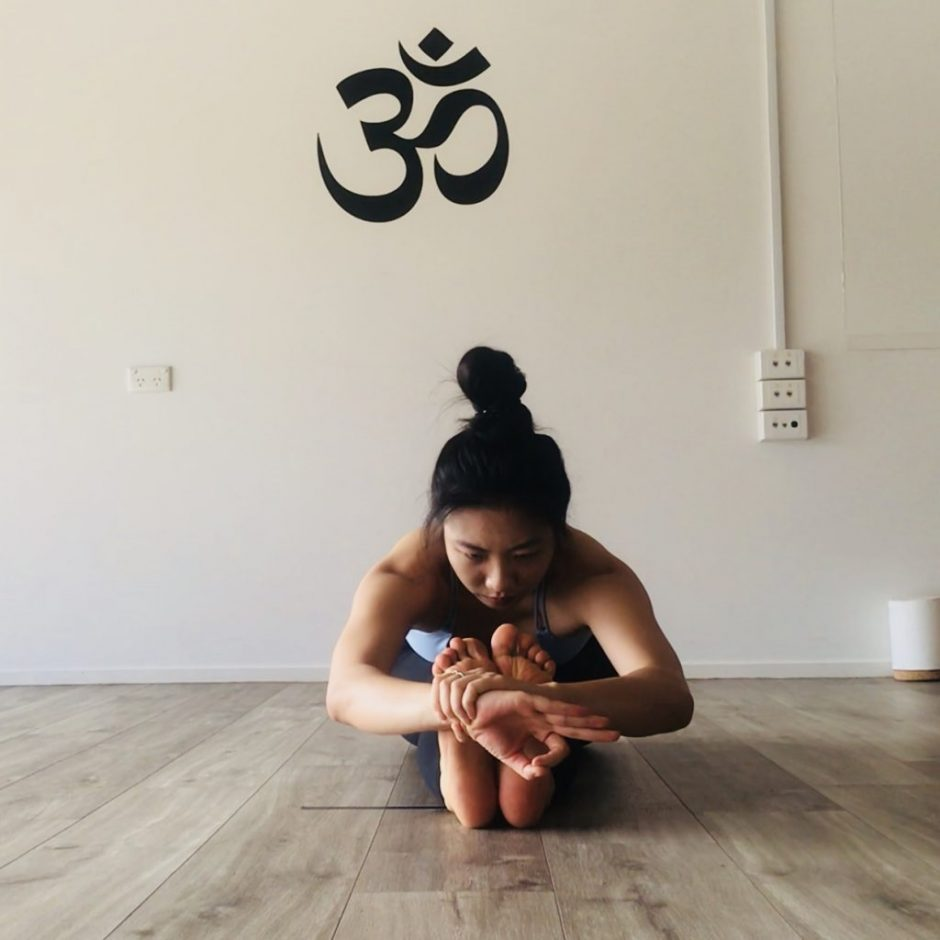 TriBalance yoga teacher Melinda Liao in seated forward bend pose